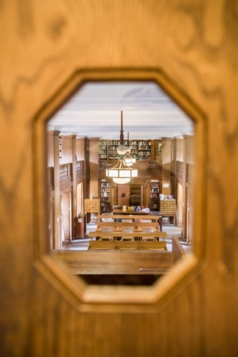 A view into the Library through a porthole in the woodwork