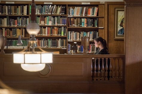 A student working at one of the Library's balcony desks