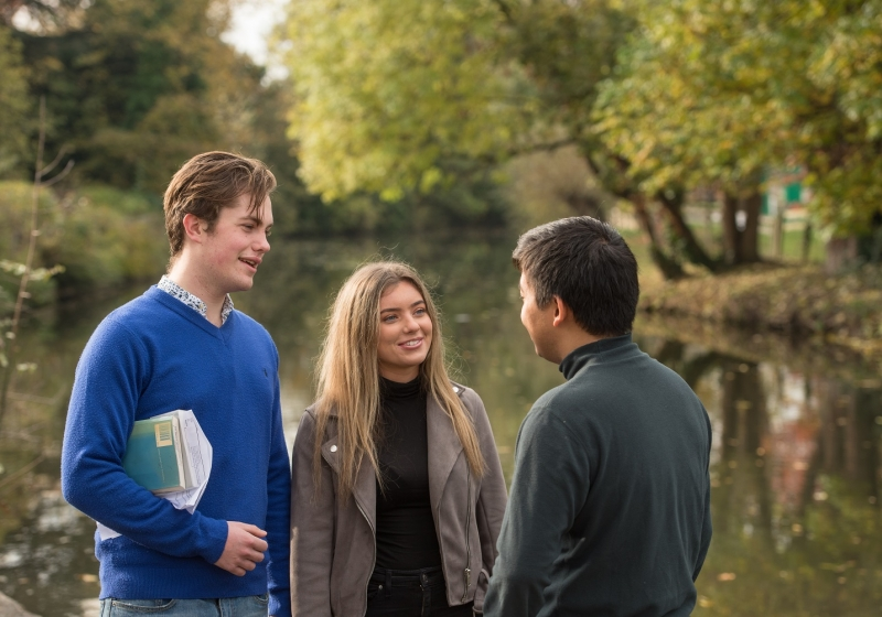 Students by the river Cherwell in the grounds of St HIlda's College